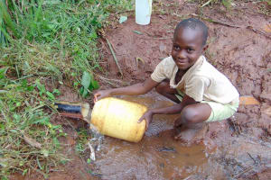 The Water Project: Masuveni Community, Masuveni Spring -  Child Fills Container At Spring Pipe