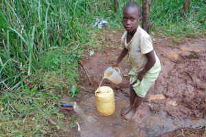 The Water Project: Masuveni Community, Masuveni Spring -  Child Fills Container With Water