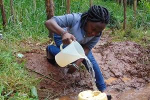 The Water Project: Masuveni Community, Masuveni Spring -  Collecting Water