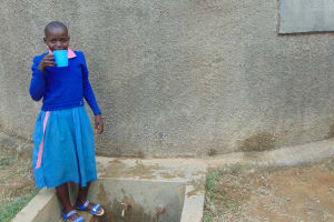 The Water Project: Naliava Primary School -  Brenda Mmbone Takes A Drink From The Rain Tank