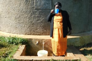 The Water Project: Eshikufu Primary School -  Head Teacher Mrs Emily Osundwa Drinks From The Rain Tank