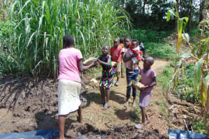 The Water Project: Shihungu Community, Shihungu Spring -  Children Bring Materials To Site