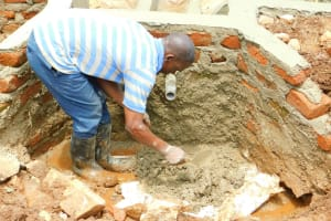 The Water Project: Lutonyi Community, Lutomia Spring -  Cementing Pipe Into The Headwall