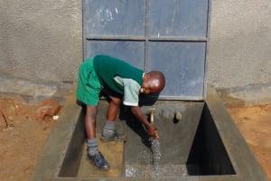 The Water Project: Lwanga Itulubini Primary School -  Student Enjoying Water From The Rain Tank