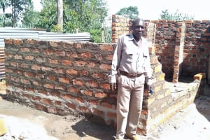 The Water Project: Friends Primary School Givogi -  Mr Henry Njosi School Chair In Front Of Latrine Construction