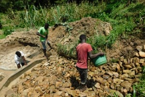 The Water Project: Ikonyero Community, Amkongo Spring -  Arranging Stones In Backfilling