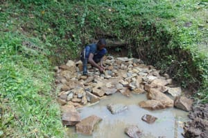 The Water Project: Buyangu Community, Osundwa Spring -  Backfilling The Spring Box With Stones