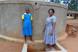The Water Project: Lugango Primary School -  Mary With Sanitation Teacher Mrs Jessica Mideva