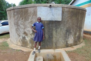 The Water Project: Shihimba Primary School -  Purity Buyanzi Stands Proud With Rain Tank