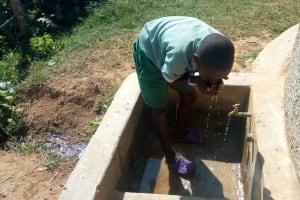 The Water Project: St. Joseph Eshirumba Primary School -  John Osaka Takes A Drink From The Rain Tank