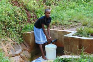 The Water Project: Musutsu Community, Mwashi Spring -  Girl Fetches Water
