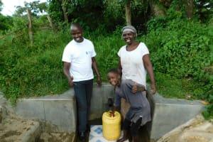 The Water Project: Muyundi Community, Baraza Spring -  Field Officer Jonathan Mutai With Jackline Baraza And Veline