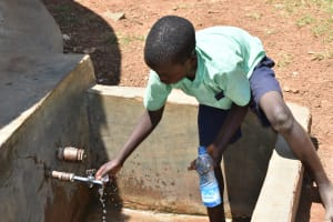 The Water Project: Mukunyuku RC Primary School -  Student Gets Water From The Tank