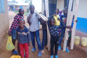 The Water Project: Friends Primary School Givogi -  Pupils Carrying Latrine Door Frame Materials