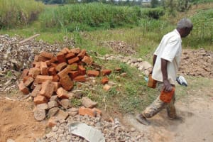 The Water Project: Ikonyero Community, Amkongo Spring -  Community Member Carries Bricks To The Site