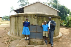 The Water Project: Emukangu Primary School, Shibuli -  Mr Imbenzi With Students At The Rain Tank