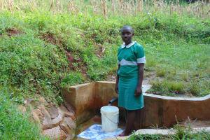 The Water Project: Musutsu Community, Mwashi Spring -  Nelly Musimbi Fetches Water