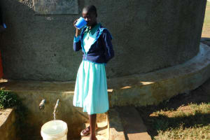 The Water Project: Eshikufu Primary School -  Vivian Osunya Drinks From The Rain Tank