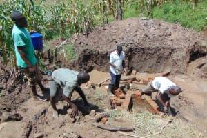 The Water Project: Shihungu Community, Shihungu Spring -  Community Members Help Lay Bricks