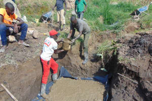 The Water Project: Sasala Community, Kasit Spring -  Adding Concrete To The Foundation