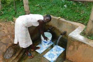 The Water Project: Irumbi Community, Okang'a Spring -  Woman Fetches Water