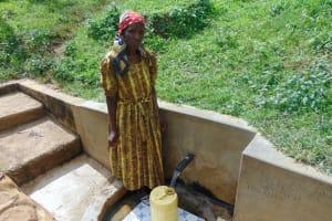 The Water Project: Isembe Community, Amwayi Spring -  Josephine Ambani Fetches Water