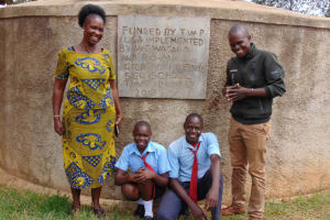 The Water Project: Gidagadi Secondary School -  Principal Alashu And Field Officer Samuel Samidi With Dominic And Another Student At The Rain Tank