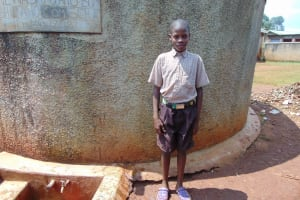 The Water Project: Shitaho Community School -  Student Stands Proud At Rain Tank