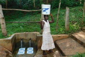 The Water Project: Irumbi Community, Okang'a Spring -  Woman Carries Water Home