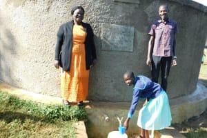 The Water Project: Eshikufu Primary School -  Head Teacher Osundwa Vivian And Field Officer Protus At The Rain Tank