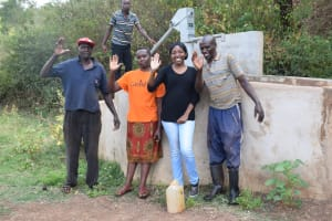 The Water Project: Masola Community A -  Field Officer Kendi Poses With Community Members At The Well A Year After It Was Constructed