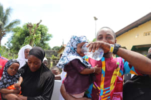 The Water Project: Lungi, Rotifunk, King Fuad Hafis Islamic School -  Young Man Joyfully Giving Child Safe And Pure Water