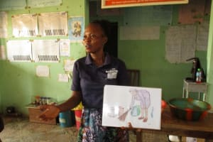 The Water Project: Targrin Health Post -  Trainer Holding Up Poster