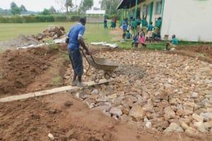 The Water Project: Elufafwa Community School -  Adding Cement To Stone Foundation Of Rain Tank