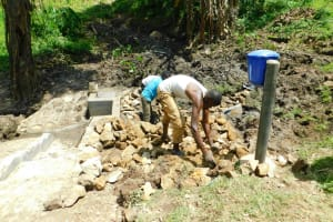 The Water Project: Bung'onye Community, Shilangu Spring -  Backfilling With Stones