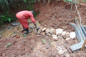 The Water Project: Shamakhokho Community, Imbai Spring -  Stone Backfilling