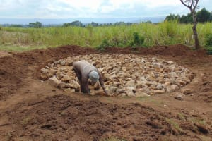 The Water Project: Mukangu Primary School -  Laying Stones For Rain Tank Foundation