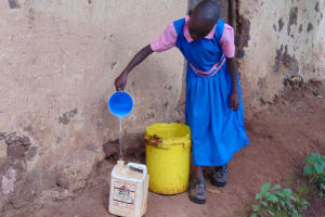 The Water Project: Kapsaoi Primary School -  Student Pours Water Into Personal Container For School