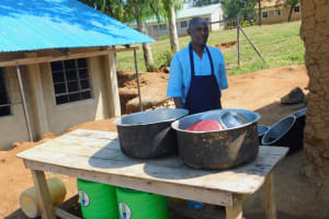 The Water Project: Ebubole UPC Secondary School -  School Cook Behind Dishrack