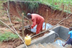 The Water Project: Shamakhokho Community, Imbai Spring -  Adding Plastic Tarp Over Backfilled Layers