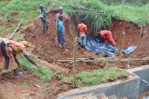 The Water Project: Shamakhokho Community, Imbai Spring -  Adding Plastic Tarp Over Backfilled Area