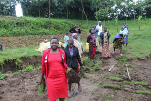 The Water Project: Emmachembe Community, Magina Spring -  Trainer Betty Carrying Grass To Be Planted