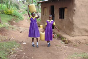 The Water Project: Kapsogoro Primary School -  Students Carrying Water From Home