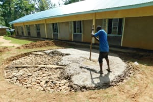 The Water Project: Enyapora Primary School -  Pouring Cement Over Stone Rain Tank Foundation