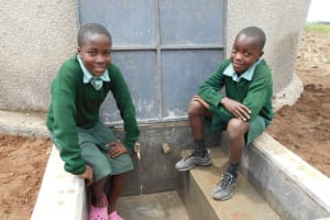 The Water Project: Mukangu Primary School -  Students Sit At Rain Tanks Tap