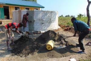 The Water Project: Mukangu Primary School -  Mixing Cement For Rain Tank Walls