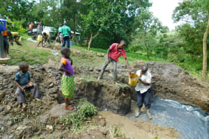 The Water Project: Bung'onye Community, Shilangu Spring -  Community Members Help Lay The Foundation