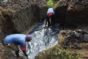 The Water Project: Emmachembe Community, Magina Spring -  Laying Plastic Tarp Before Laying Foundation
