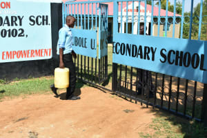 The Water Project: Ebubole UPC Secondary School -  Student Carrying Water