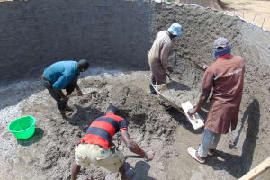 The Water Project: Mukangu Primary School -  Teamwork Cementing Inside The Tank